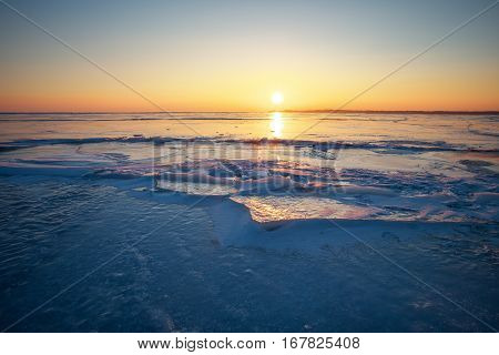 Beautiful winter landscape with sunset fiery sky and frozen lake. Composition of nature.