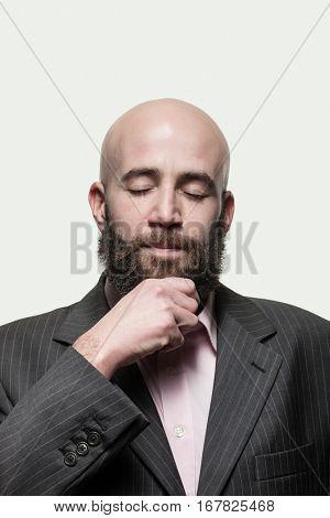 Man scratches his beard,  wearing a stylish jacket and pink shirt