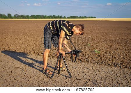 Photographer takes pictures ground textures in hot day. The men with the camera in a field. Man working in nature.