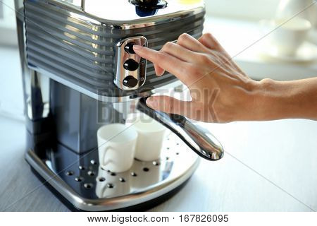 Woman making aromatic espresso in coffee machine, closeup