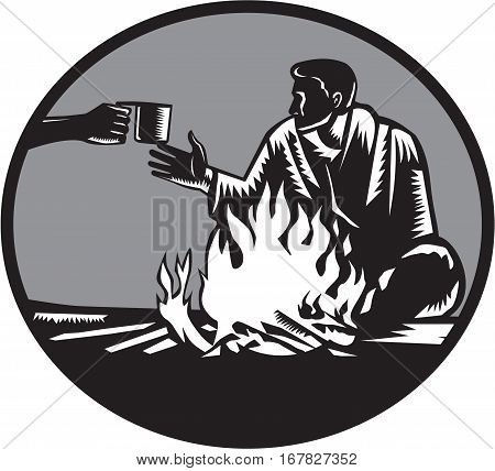Illustration of camper with a sleeping bag wrapped around his shoulders holding on tight sitting in front of a fire accepting a tin cup of hot coffee set inside circle done in retro woodcut style.