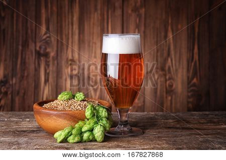 Glass of dark beer, barley and hop cones on table against blurred wooden background