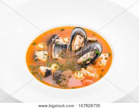 Fish soup with fish and oysters into plate