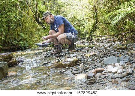An image of a man doing gold panning in New Zealand