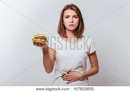 Image of confused young woman with painful feelings standing over white background while holding fastfood and touching belly