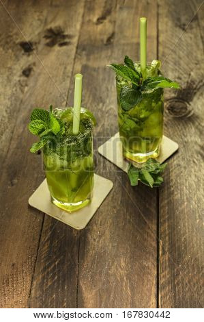 A photo of mojito cocktails with mint leaves, wedges of lime, and drinking straws, on a dark wooden background with copy space