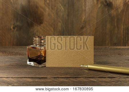 A photo of a blank brown kraft business card on a dark wooden background texture with a golden ink pen and ink bottle. A mockup or a minimalist banner with copy space