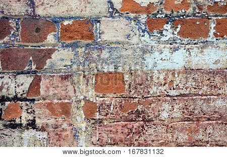 Old cracked rendered wall from historic building with exposed brick and mortar and peeling paint. Grunge texture background