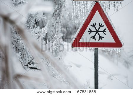 Traffic sign for icy road with sleet covered trees. Danger on the road black ice danger wintertime concept.