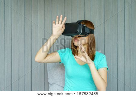 Young woman in virtual reality glasses touching something with her hand at home