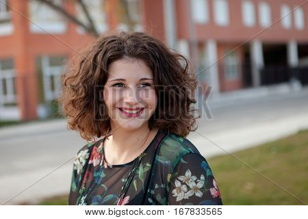Happy curvy girl with curly hair in the street with a flowered dress