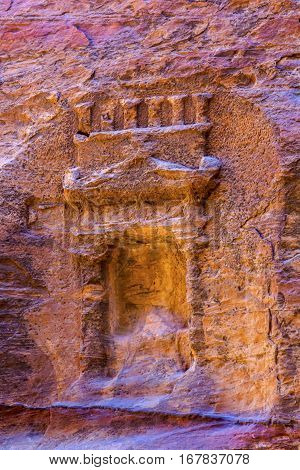 Small Rose Red Rock Tomb Outer Siq Canyon Petra Jordan. Built by the Nabataens in 200 BC to 400 AD. Rose Red canyon walls create many abstracts close up. Inside the Tombs the rose red can become blood red. Reds are created by magnesium in sandstone.