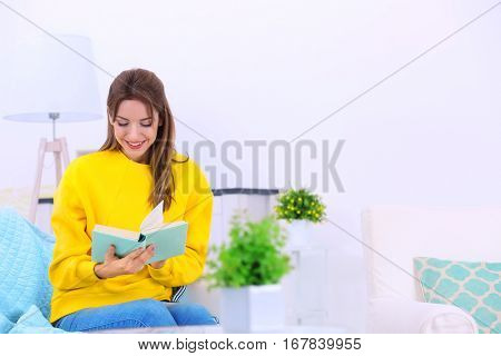Young woman reading interesting book on sofa at home