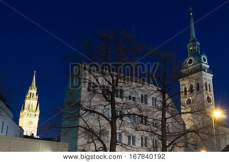 MUNICH - JANUARY 29: Night shot of St. Peter's Church (Peterskirche) on the right and Rathausgalerie in Marienplatz in Munich Germany