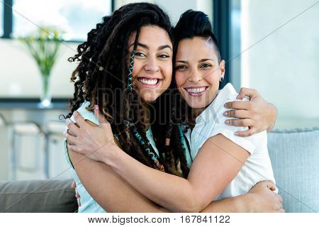 Portrait of happy lesbian couple embracing each other and smiling in living room