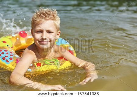 Boy in the water with a floating ring learning how to swim in summer
