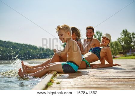 Happy family splashing water with their feet at a lake on their holidays