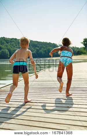 Two kids from the back running and playing on a pier at the lake in summer