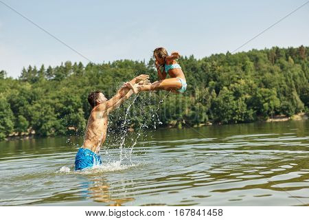 Father throwing daughter into the water in summer and having fun during their holidays