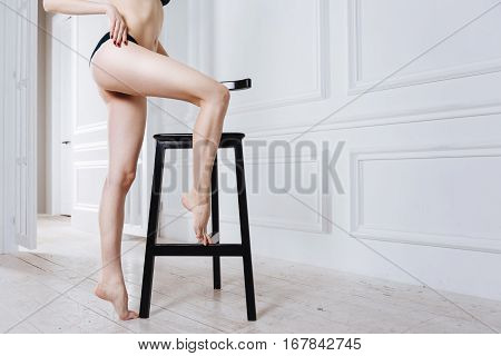 Pose on tiptoes. Slim female wearing black underwear standing on wooden floor holding right leg on the chair while touching herself