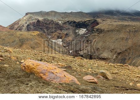 Beautiful scenery slopes of the volcano Mutnovsky with clouds.