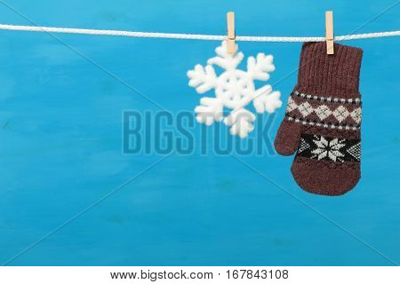 Mitten with snowflake hanging on the clothesline on blue wooden background