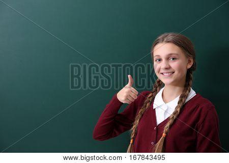 Teenage girl standing near green school blackboard