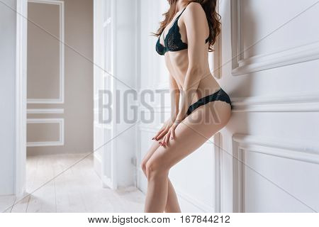 Enjoy the photo shoot. Cute young model wearing lace glamour lingerie standing in flexible position while holding hands on her legs