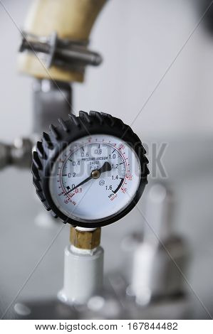 Closeup of pressure vacuum gauge with tube on background