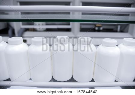 Row of empty plastic bottles on production line