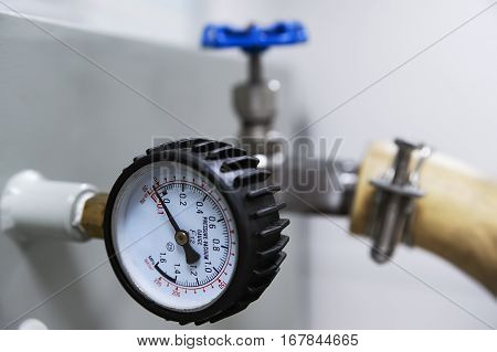 Closeup of pressure vacuum gauge and blue valve