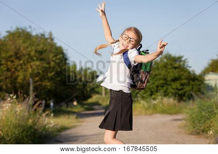 Smiling Young School Girl In A School Uniform Jumping On The Road