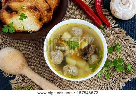 Light soup with dried mushrooms meatballs and maccheroni in a white bowl. The top view