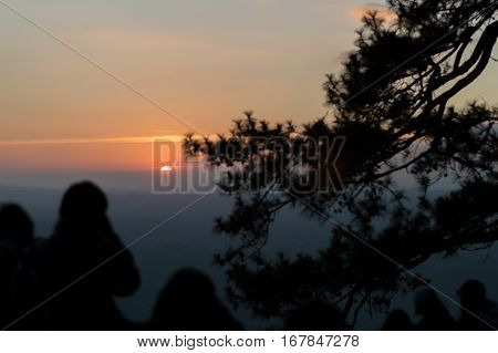 (selective Focus Of Sun) Many Tourists Standing On The Top Of The Mountain Looking Sunset At Pha Lom