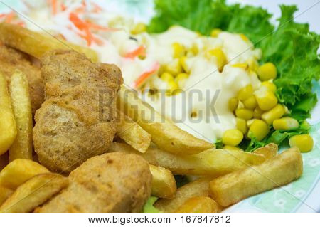Vegetable Salad French Fries And Chicken Nuggets.