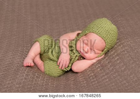 Cute newborn in a knitted green hat sleeping on a soft blanket