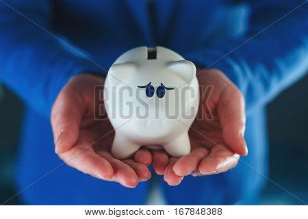 Sad piggy coin bank in businesswoman's hands desperate look on face