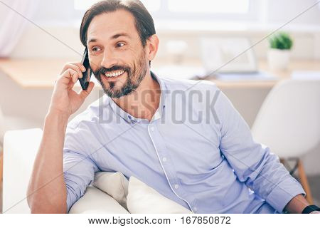 Pleasant conversation. Cheerful content smiling adult man talking on cell phone and expressing gladness while resting on the couch