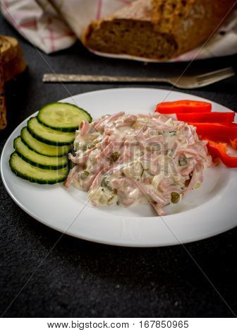Mayonnaise mixed salad with vegetables and sausage nad baquette