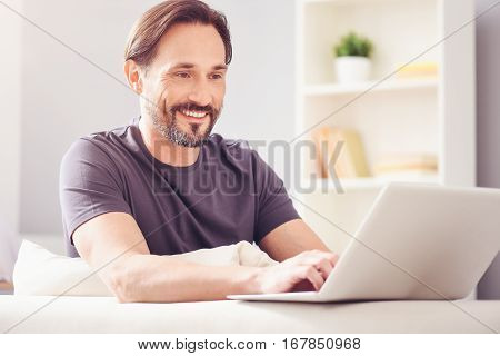 Inspiring work. Positive delighted adult handsome man sitting at the table and usanf laptop while working at home