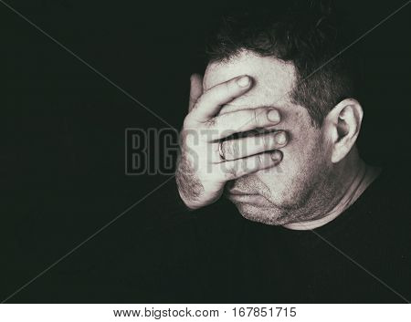 Portrait of pensive sad middle-aged men. He covered his face with his hands. Black and white monochrome photo