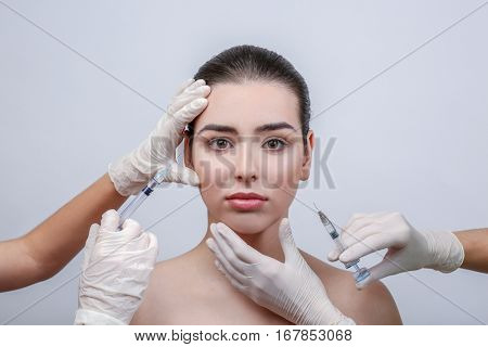 Beautiful young woman receiving filler injections in face, on light background
