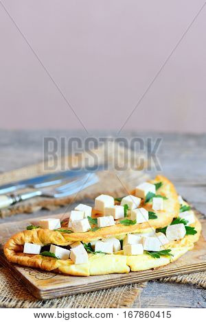 Healthy tofu omelette on a wooden board. Fried omelette stuffed with tofu and fresh parsley. Fork and knife on a wooden table. Culinary background with empty place for text. Vegetarian low fat recipe