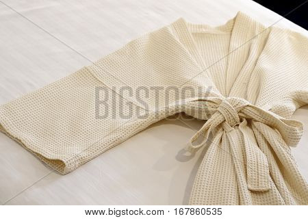 photo of white bathrobe on the bed