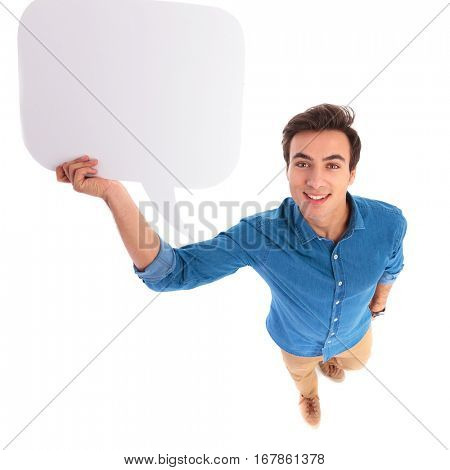 smiling young casual man holding a speech bubble above his head, isolated on white background