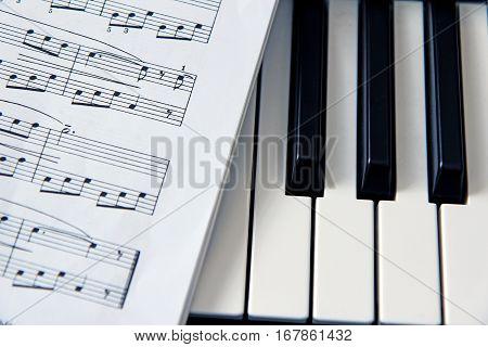 close-up white music score on piano keyboard