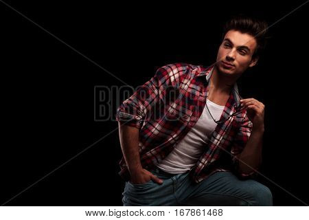 side view of a sexy young casual man taking off his glasses and looks away from the camera