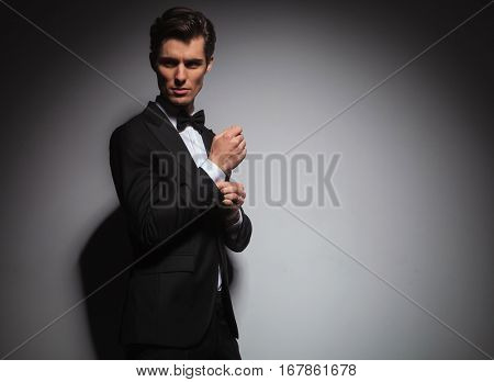 attractive young man in tuxedo and bowtie arranging his sleeve  looks back over his shoulder, standing in studio against grey background