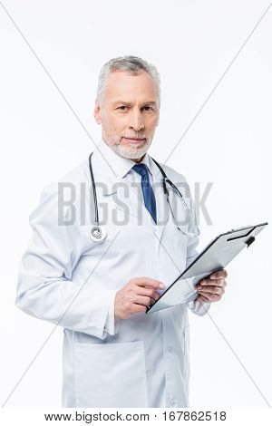 Smiling male doctor practitioner holding clipboard and looking at camera