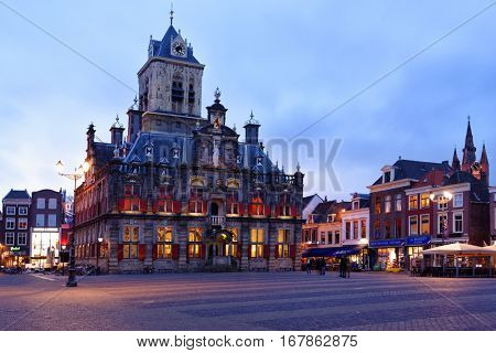 DELFT, NETHERLANDS - JANUARY 3, 2017: People on the Markt square in front of the City Hall. Built in 1620, it was heavily changed and was restored in the 20th century to its Renaissance appearance